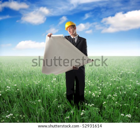 Architect observing a plan on a green meadow - stock photo