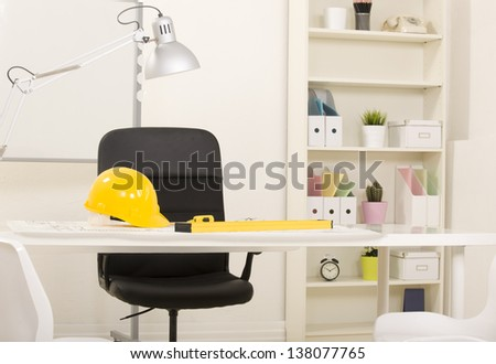 Architect office view with project whiteboard, hardhat and equipment on desk - stock photo