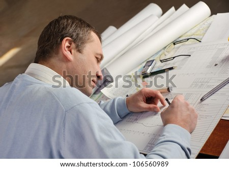 Architect or constructor in blue pullover is working on construction plans. - stock photo