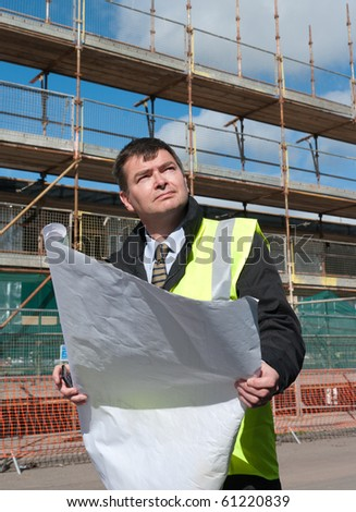 Architect or engineer at work on a building site. Checking plans against the construction work. Confident gaze. - stock photo