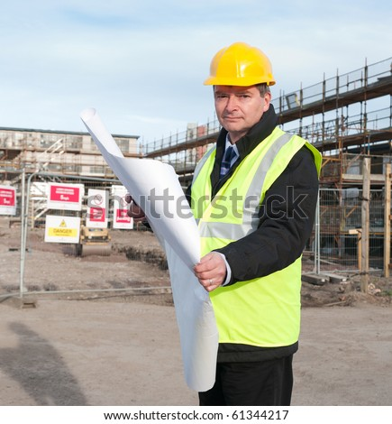 Architect or engineer at work on a building site. Checking plans against the construction work. Looking confidently at camera. - stock photo