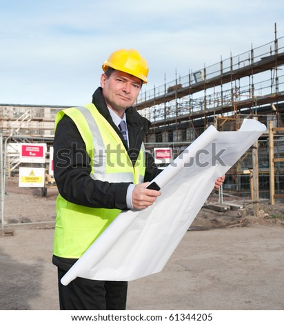 Architect or engineer at work on a building site. Holding plans for construction work. Confident gaze and smile at camera.