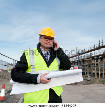 Architect or engineer at work on a building site. Holding plans for construction work. Confident gaze and smile at camera. Using telephone. - stock photo