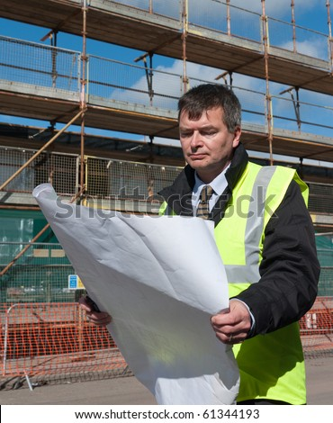 Architect or engineer at work on a building site. Looks down at plans of construction work. Concentrating. - stock photo