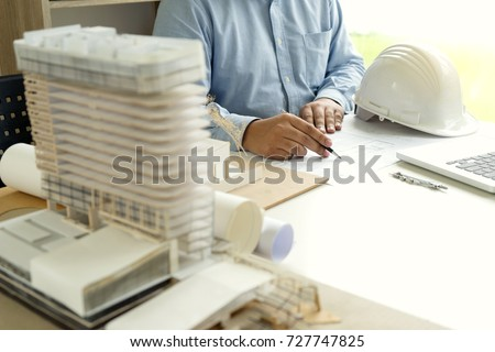 Architect or engineer hand on the table with home model