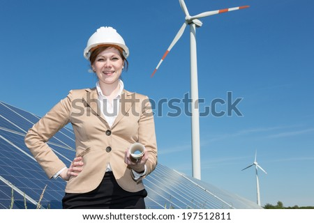 Architect or engineer posing at solar panels in wind farm - stock photo