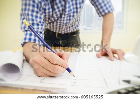 Architect or engineer working in office with blueprints,engineer inspection in workplace for architectural plan,sketching a construction project,Business construction concept.
