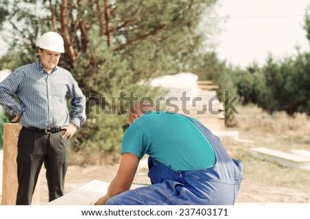 Architect or foreman watching a builder drilling a hole in a large wooden beam, view over the workmans shoulder - stock photo