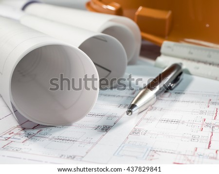 Architect plan rolls and pen with orange hat (Selective focus) - stock photo