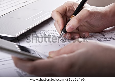 Architect reviewing a blueprint by adjusting the measurement with a pen, smart telephone and laptop - stock photo