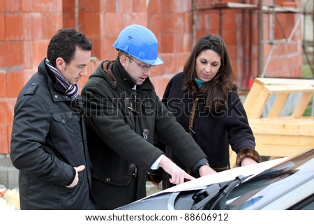 Architect reviewing a building plan with his clients - stock photo
