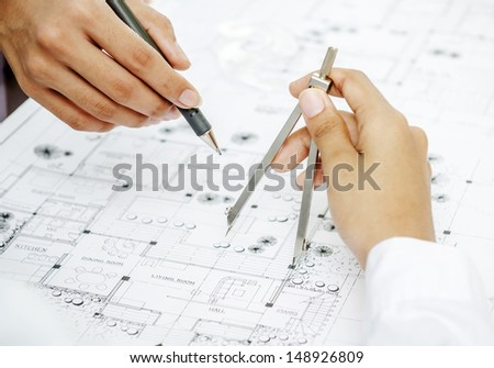 Architect reviewing blueprint by adjusting drawing compass - stock photo