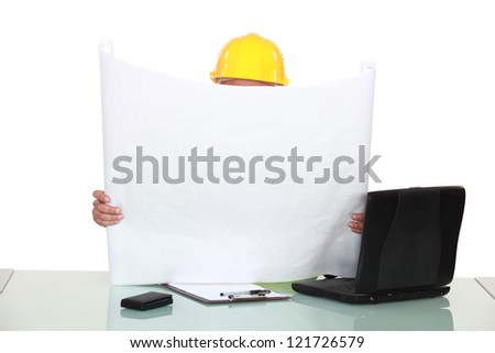 Architect sat at desk reading plans - stock photo