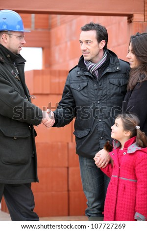 Architect shaking hands with a young family on site - stock photo