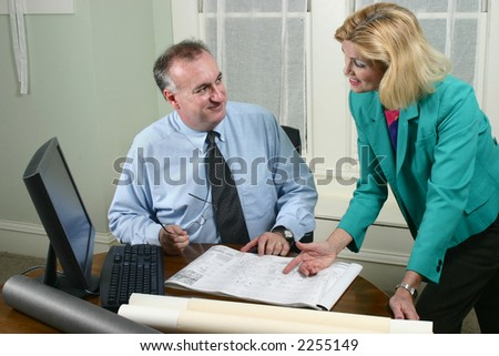 Architect showing client blueprints in the office.  Landscape horizontal orientation. - stock photo