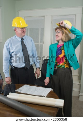 Architect showing client blueprints in the office.  Wearing hardhats in preparation for a visit to the construction site. - stock photo