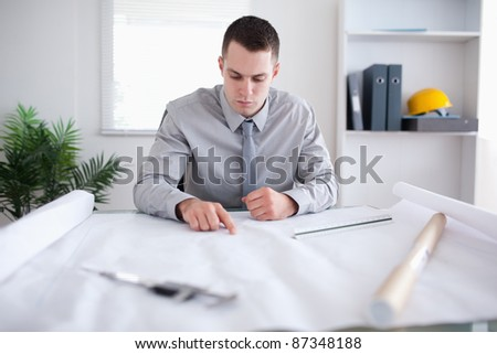 Architect sitting behind a table and working on a construction plan