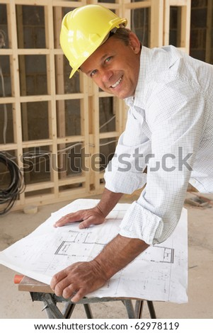 Architect Studying Plans In New Home - stock photo