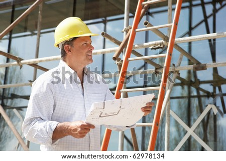 Architect Studying Plans Outside New Home - stock photo