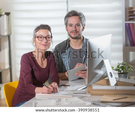 Architect team, one woman and one man, sitting at office, working on blueprints for a new building project. They wear casual clothes
