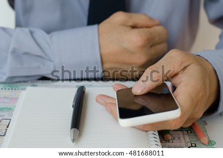 Architect using mobile smartphone at office, working on plan.