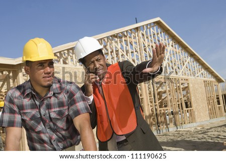 Architect using phone with co-worker standing by at construction site - stock photo