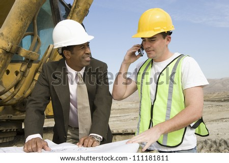Architect wearing hard hat at construction site - stock photo