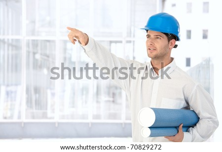 Architect wearing hardhat holding work plan standing in office, pointing.? - stock photo
