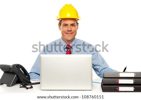 Architect wearing safety hat and using laptop in office. Studio shot - stock photo