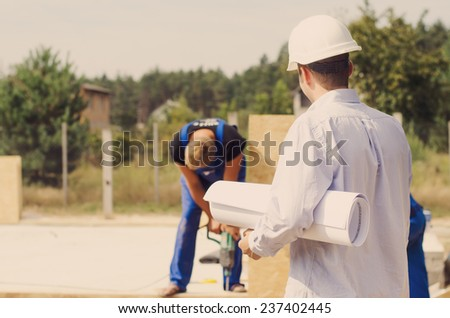 Architect with a blueprint rolled up under his arm standing watching the builders at work on a residential building site - stock photo
