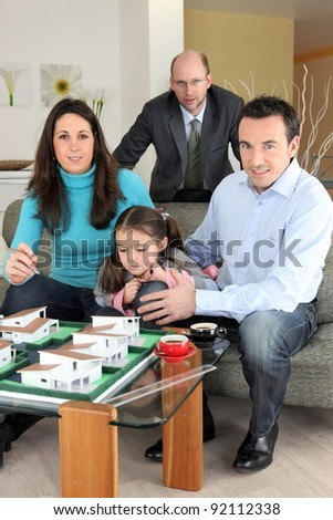 Architect with a family looking at a construction model - stock photo