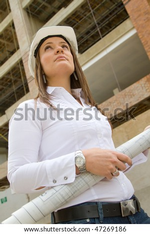 Architect with blueprints at a construction site - stock photo