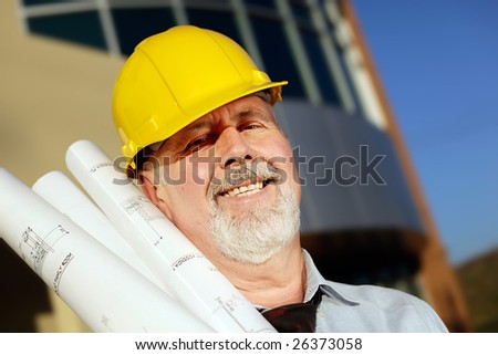 Architect with blueprints in a hardhat in front of a modern building
