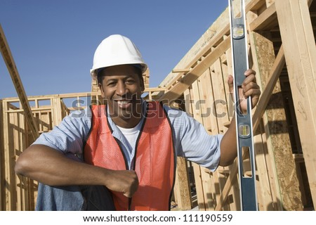 Architect with bubble level at construction site - stock photo