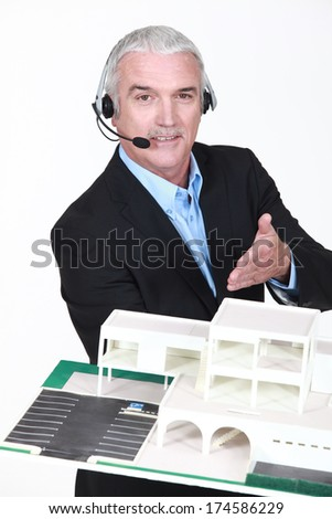 Architect with headset showing model - stock photo