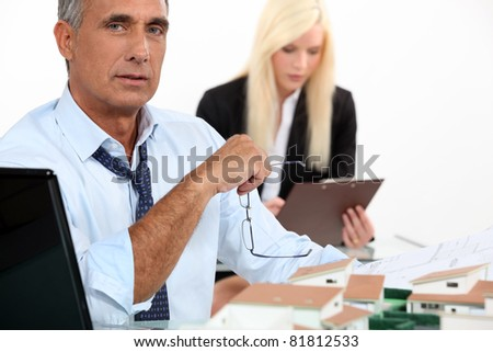Architect with model of housing development and assistant - stock photo