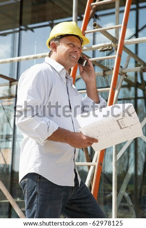 Architect With Plans Outside New Home Talking On Mobile Phone - stock photo