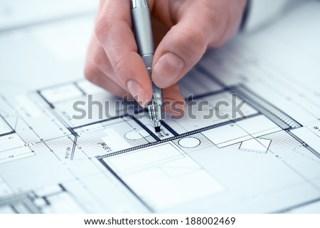 Architect Woman drawing on print construction project - stock photo
