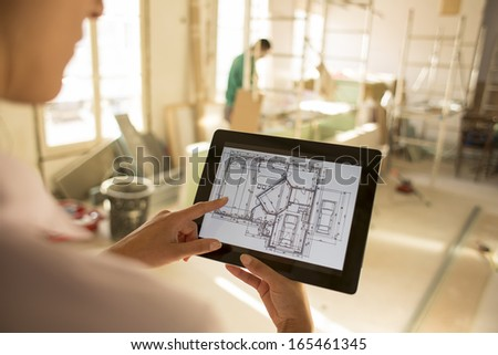 Architect woman working with electronic tablet, on site - stock photo