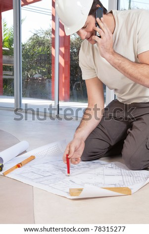 Architect working on blueprint and talking on cellphone - stock photo