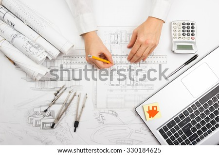Architect working on blueprint. Architects workplace - architectural project, blueprints, ruler, calculator, laptop and divider compass. Construction concept. Engineering tools - stock photo