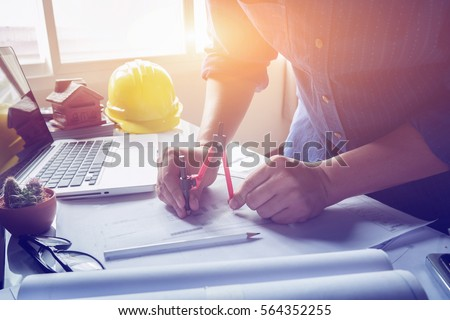 Architect working on blueprint. Architects workplace - architectural project, blueprints, ruler, calculator, laptop and divider compass. Construction concept. Engineering  tools,selective focus