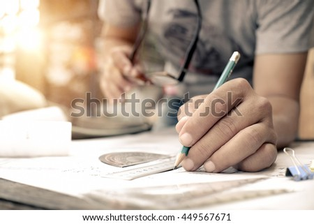 Architect working on blueprint. Architects workplace - architectural project, plan, drawing, sketch, ruler, calculator and divider compass. Construction concept.Architects working - stock photo