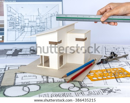 Architect working with small house model & blueprints/ home renovation concept - stock photo