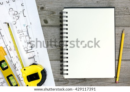 architect workspace with blueprint, tools, notepad and pencil on gray wood - stock photo