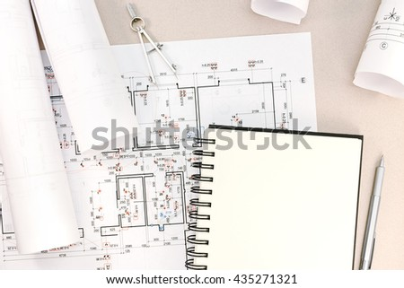 architect workspace with blueprints, rolls, notepad, drawing compass and pencil - stock photo