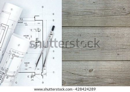 architect workspace with plan, rolls of blueprints and drawing compass - stock photo