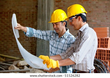 Architects at a construction site looking at blueprints - stock photo