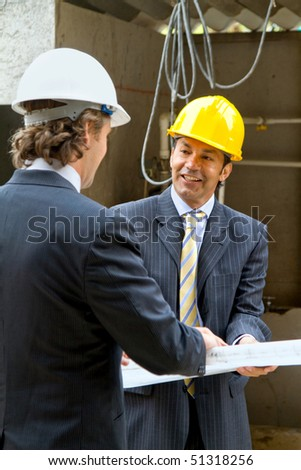 Architects at a construction site looking at the blueprints