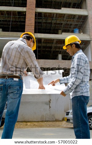 Architects at a construction site looking at the blueprints - stock photo
